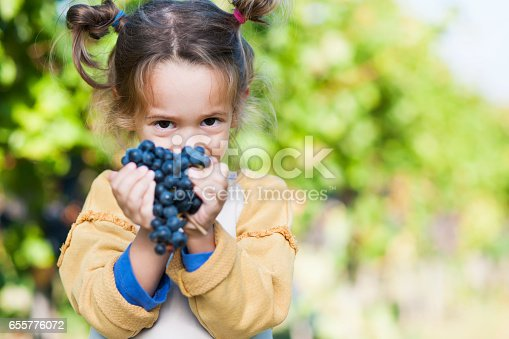 Little girl with her grandmother love spending time together in vineyard