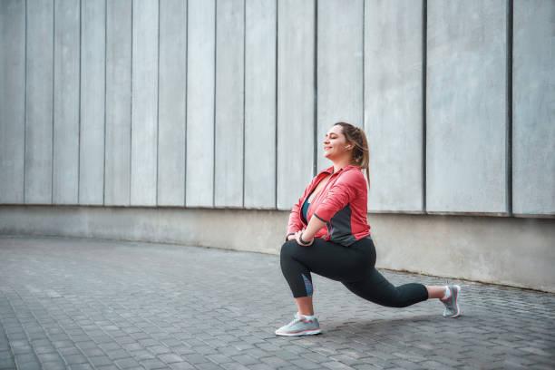 私はスポーツハッピープラスサイズの女性が灰色の壁に立ちながらストレッチエクササイズや笑顔をするスポーツ服を着て大好きです。 - real bodies ストックフォトと画像