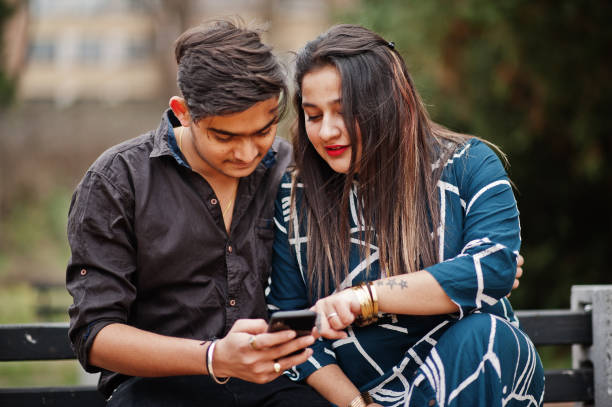 Love story of indian couple posed outdoor. Indian couple posed outdoor, sitting on bench together and looking at mobile phone. romance stock pictures, royalty-free photos & images