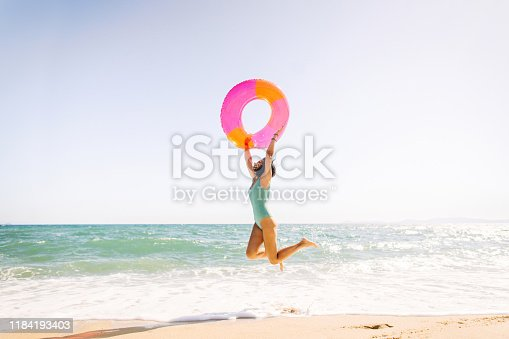 Photo of young woman having fun at the beach
