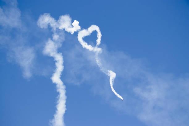liebe symbolischen herzform aus weißen rauchfahne am himmel von einer schallmauer - schrift am himmel stock-fotos und bilder