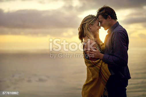 Shot of an affectionate young couple sharing a tender moment at sunset