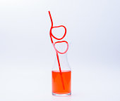 A heart shaped straw in drink glass half full