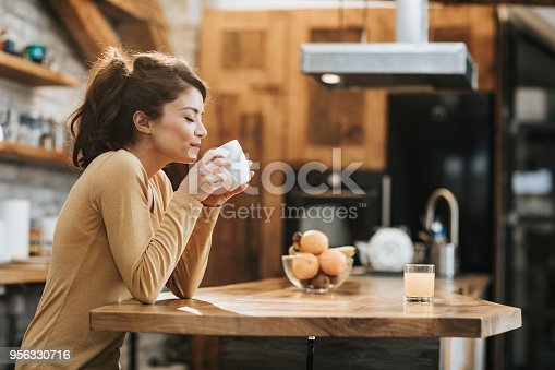 Young woman enjoying in a smell of fresh coffee in the kitchen.