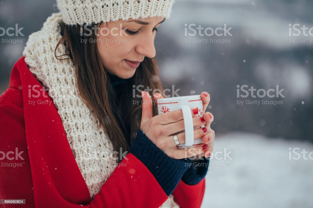 Woman standing in the snowy outdoors and drinking hot drink