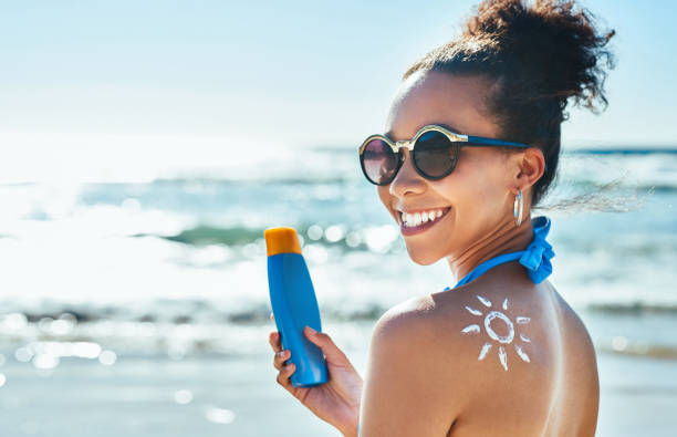 I love the sun but I love my skin more Portrait of a beautiful young woman with a sun drawn on her shoulder with sunscreen at the beach suntan lotion stock pictures, royalty-free photos & images