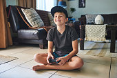 Full length portrait of a young boy playing video games at home