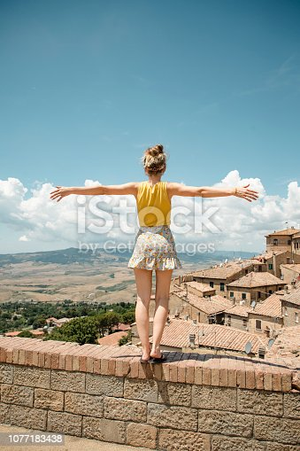 One young woman is standing on a wall in Volterra with her back to the camera and her arms outstretched.