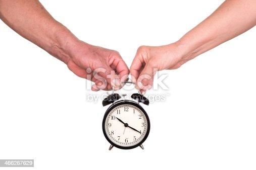 love time:senior couple holding clock ioslated on white background