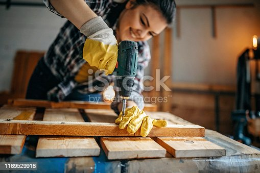 Woman screwing screws in lath to make table