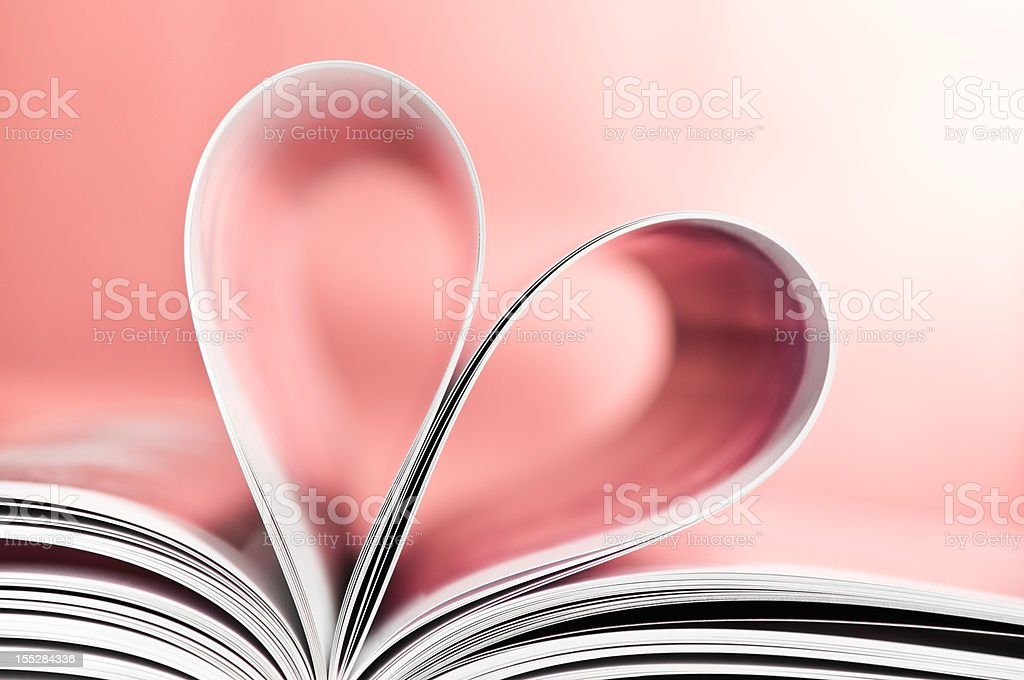 Love to read, pages folded into heart shape, pink background stock photo