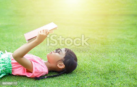 Little girl lay on grass and reading a book in a summer day