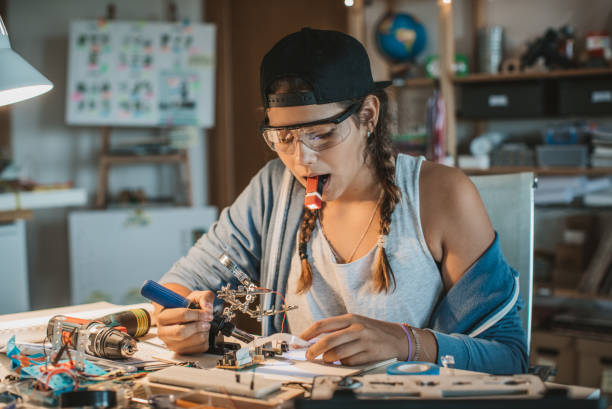 Love to repair things Teenage girl working on some engineering project at home.  Working table full of different tools and items needed for repairing electrical circuits. soldering iron stock pictures, royalty-free photos & images
