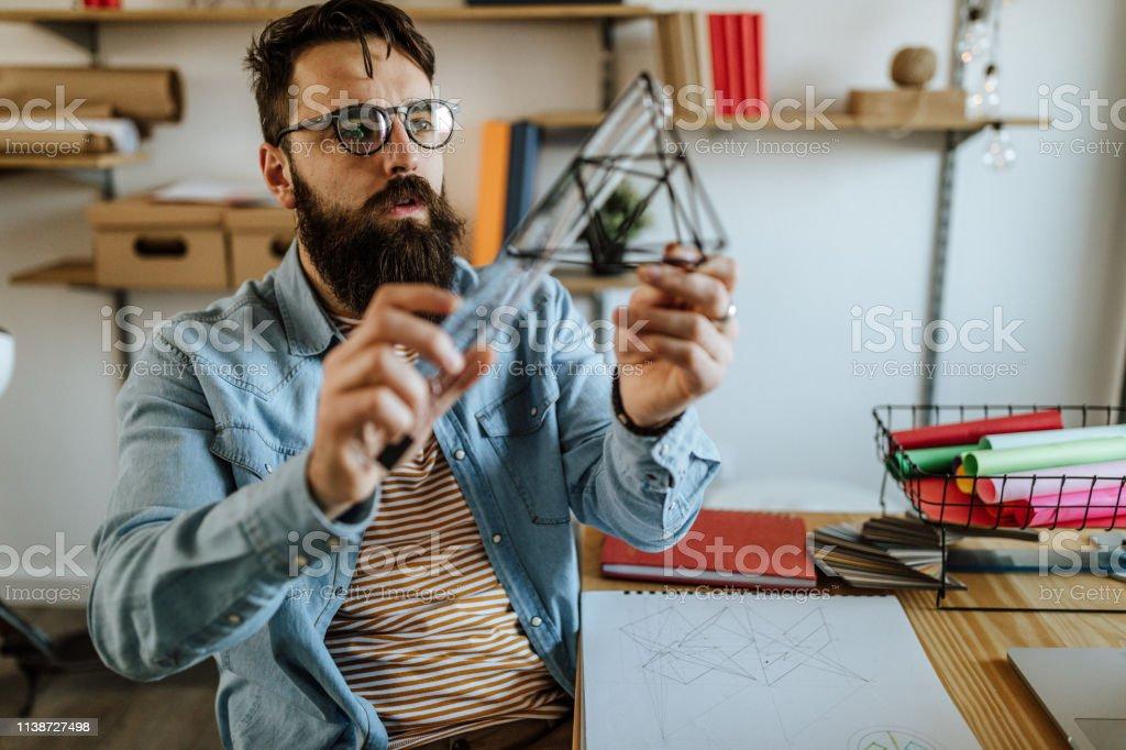 Bearded men examining 3D object