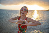 Portrait of young woman wearing heart shape red sunglasses at sunset on beautiful beach making heart shape frame with hands - Saint Valentine concept