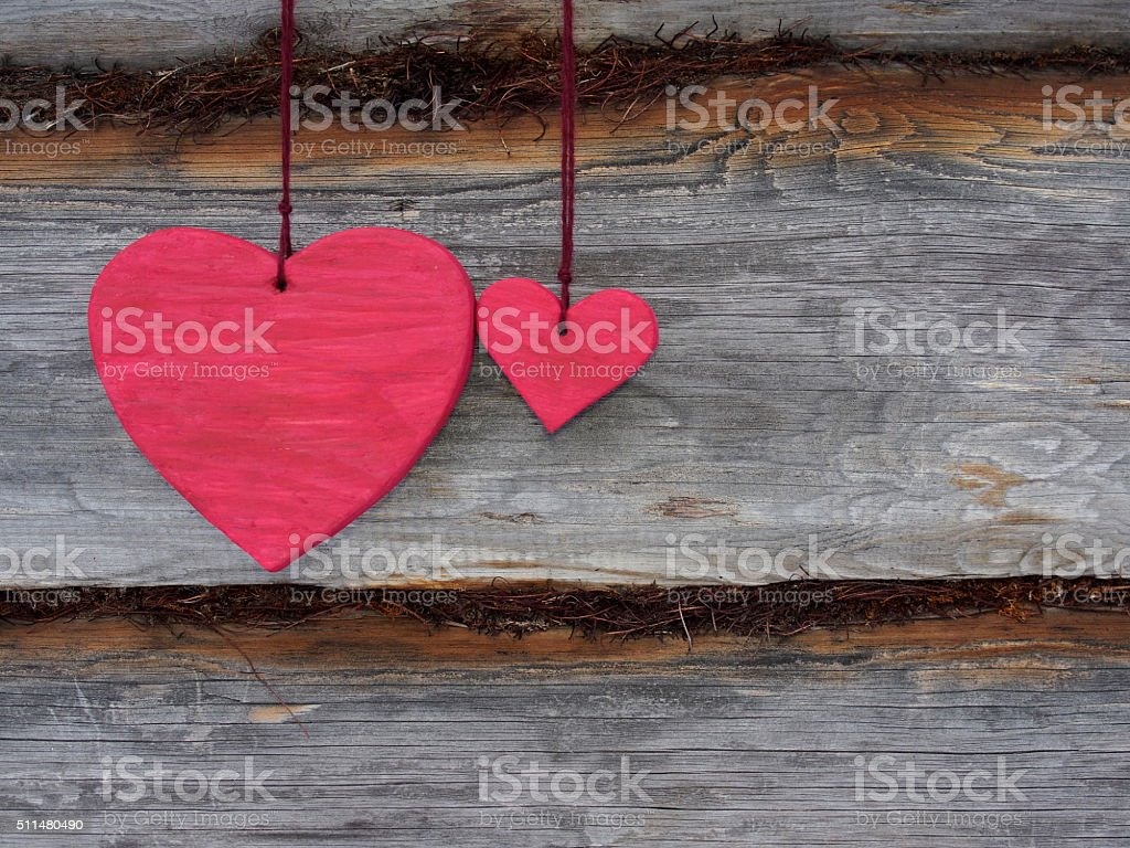 Love Valentine's hearts hanging on rustic balk texture backgroun stock photo