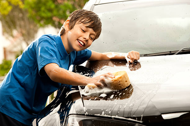I love washing Dads car! Cute boy washing a car on a hot summers day. allowance stock pictures, royalty-free photos & images