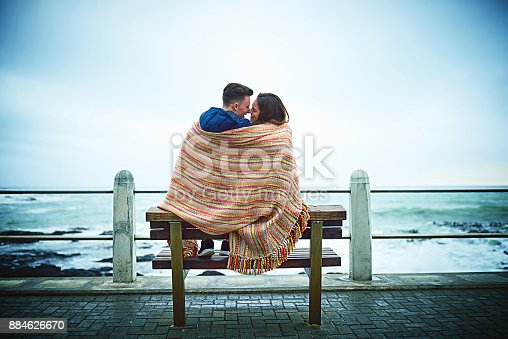 Shot of a happy young couple covering themselves with a blanket outdoors