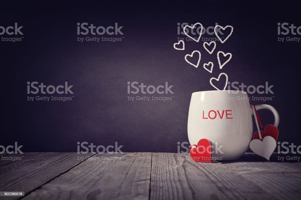 Love written on a mug concept for Valentines day or Mothers day background with copy space