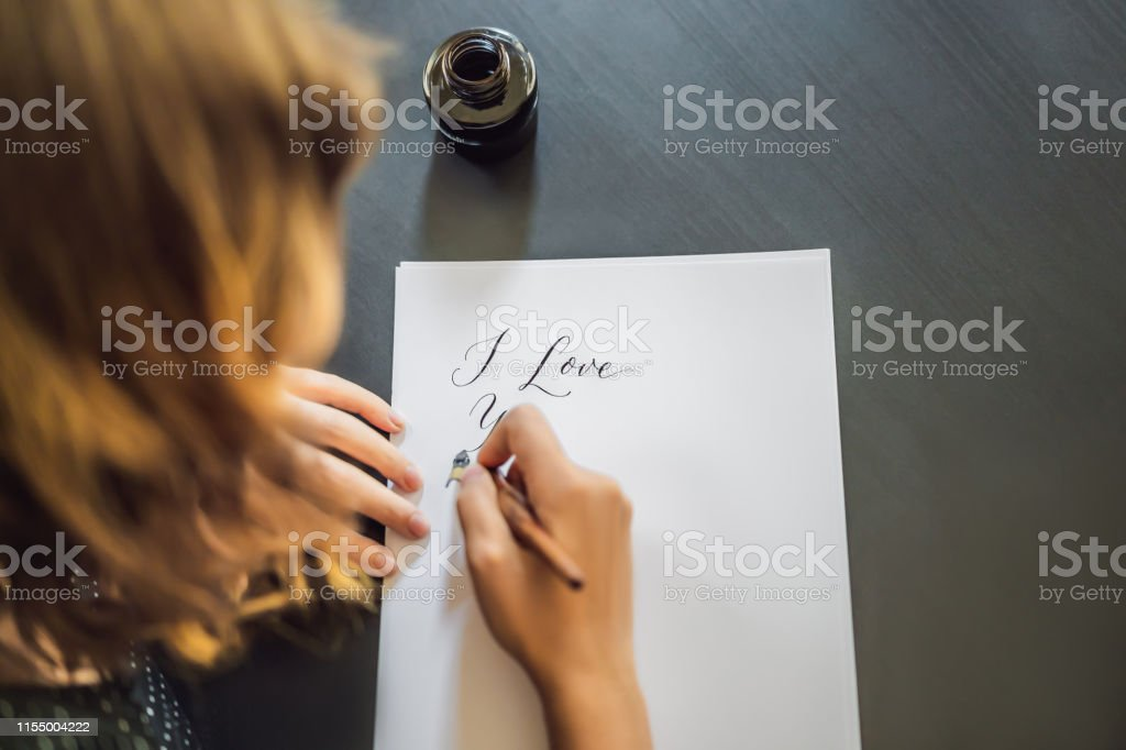 I love you. Calligrapher Young Woman writes phrase on white paper....