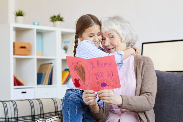 I Love You Card for Grandma Portrait of cute little girl hugging grandma and giving her handmade I love you card on Valentines day, copy space granddaughter stock pictures, royalty-free photos & images