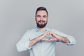 istock I love you! Close up photo portrait of handsome attractive honest kind with bristle stubble toothy beaming grinning cool human he him give demonstrate small little blue heart isolated grey background 1069577532