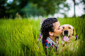 Young woman and her labrador dog having fun and playing in grass
