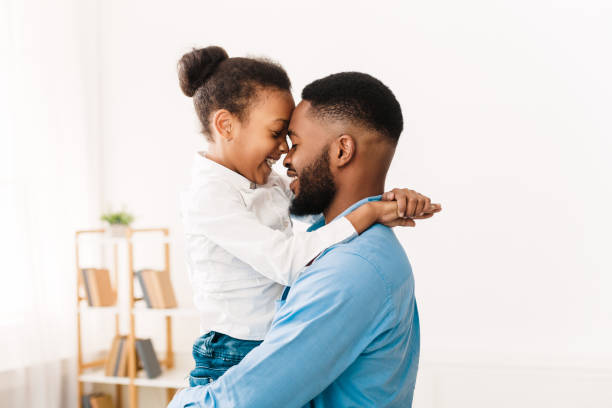 I love you, dad. Man hugging his little cute girl I love you, dad. African-american daughter hugging father at home genderblend stock pictures, royalty-free photos & images