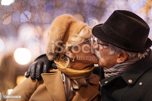 Happy senior adult couple kissing outdoors at winter