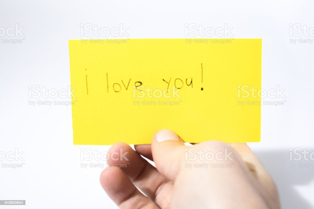 I love you handwrite with a hand on a yellow paper composition stock photo