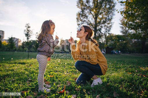 Mother and daughter playing around and relaxing in a public park together