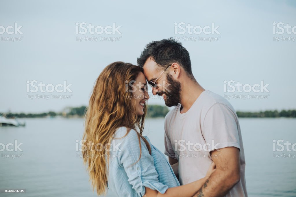 I love you Lovers in the warm embrace enjoy the sunset and the sandy banks of the river. They are in love and decided to spend a beautiful summer day at the beach. Agricultural Field Stock Photo
