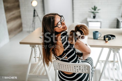 Woman with her dog, enjoying day in home office