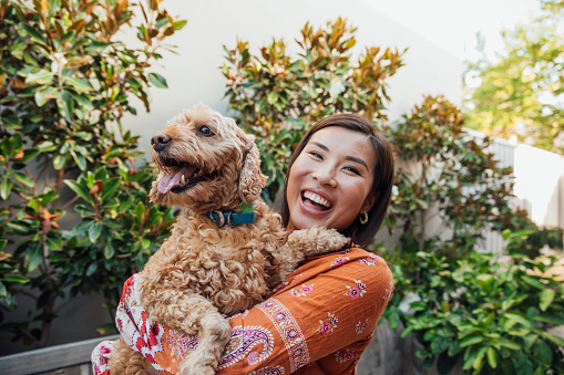 A shot of a young, Asian woman smiling at the camera with her dog.