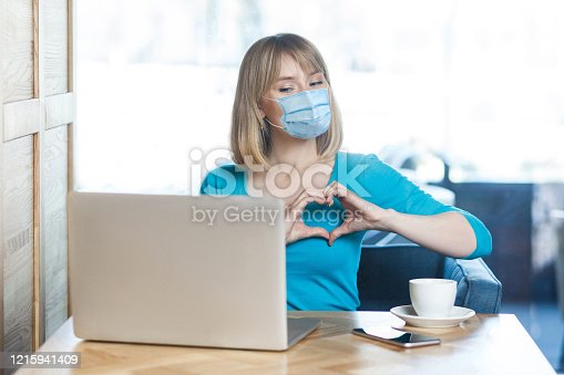 I love you. Portrait of young woman with surgical medical mask sitting and looking at laptop display with heart gesture on video call. Indoor distance working, medicine and health care concept.
