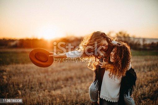 Two beautiful women having fun in meadow