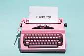 Pink vintage typewriter with a white sheet of paper and 'I love you' written on it. Love concept.