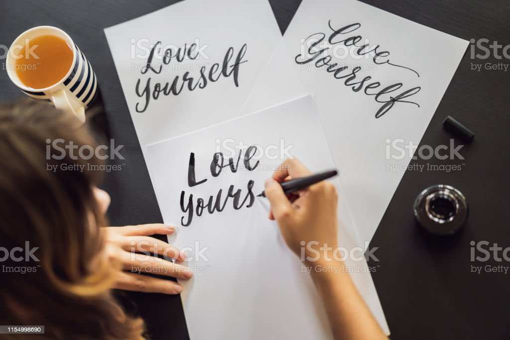 Love yourself. Calligrapher Young Woman writes phrase on white paper....