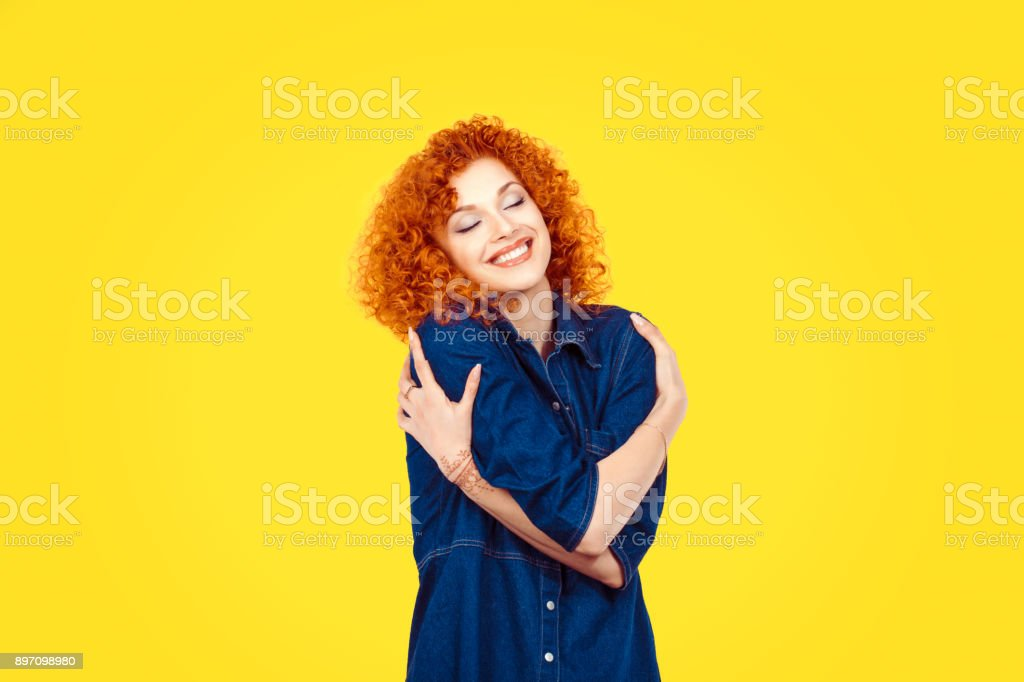 Love yourself concept. Closeup portrait confident smiling woman holding hugging herself isolated yellow wall background. Positive human emotion, facial expression feeling reaction situation attitude stock photo