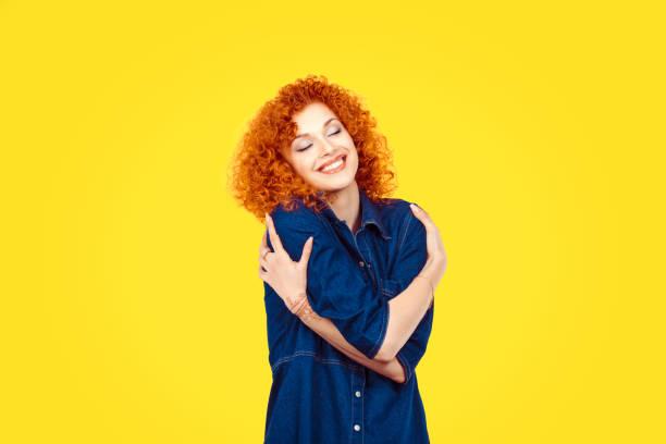 s'aimer soi-même concept. closeup portrait confiante femme souriante tenant étreindre elle-même isolée fond mur jaune. émotion humaine positive, attitude de situation expression faciale sentiment réaction - femme seule s'enlacer photos et images de collection