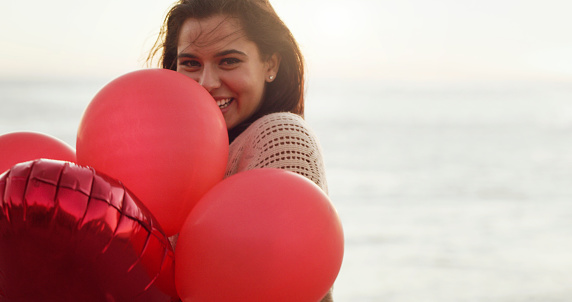 Cropped shot of a beautiful young woman holding a bunch of balloons