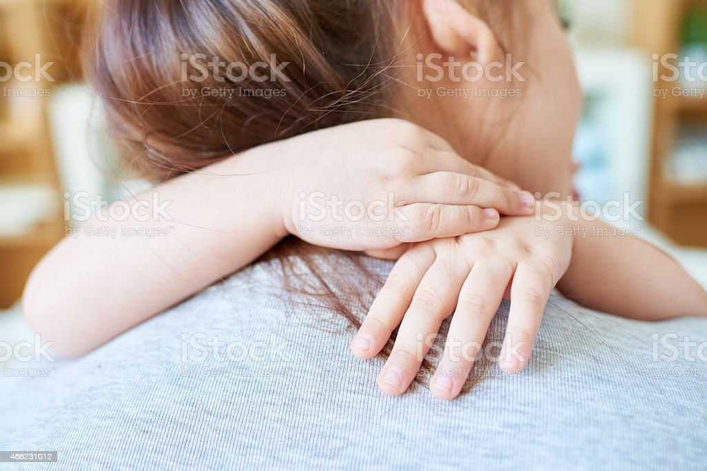Loved by daughter Rear view of woman embraced by her little daughter 2015 Stock Photo