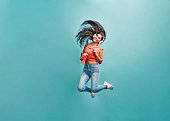 Love,enjoy and lifestyle concept.Beautiful energy girl with white headphones listening to music laughs and jump on blue background in studio. Long hair in is flying from moving.Copy space.
