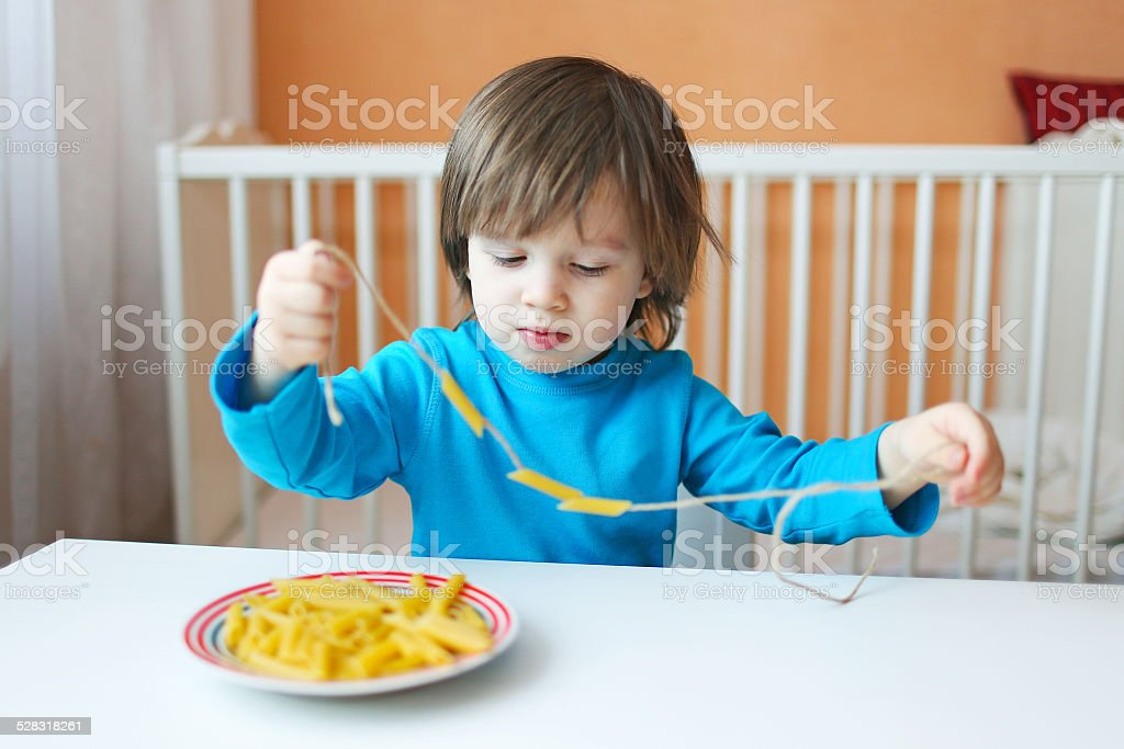 lovely 2 years boy made macaroni beads stock photo