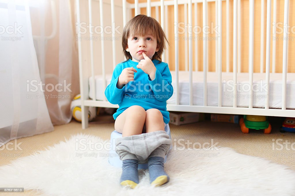 Lovely 2 years boy sitting on potty stock photo