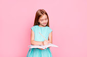 istock Lovely adorable charming little girl is looking down at the copybook in her hands and writing information there, she is wearing light blue dress, isolated on bright pink background, copyspace 926555352