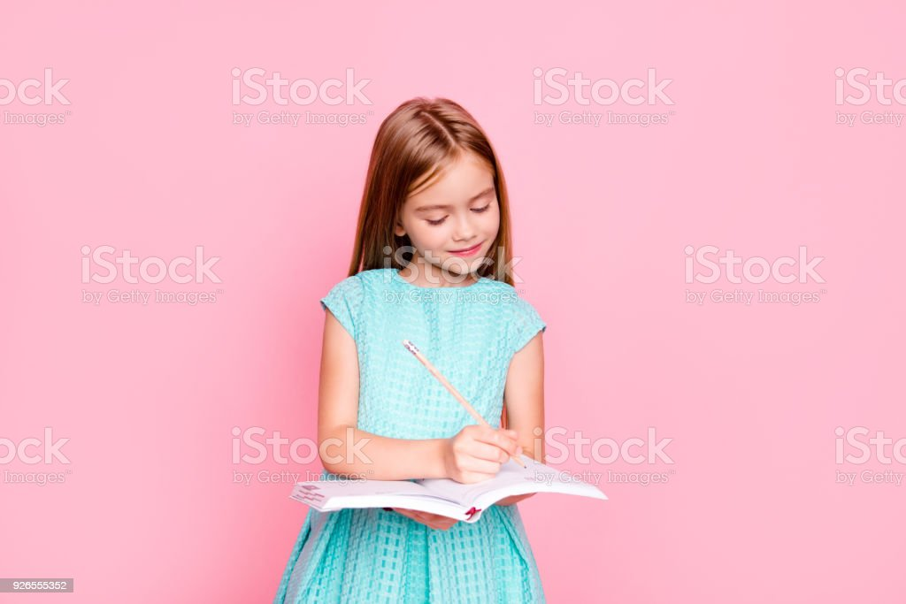 Lovely adorable charming little girl is looking down at the copybook in her hands and writing information there, she is wearing light blue dress, isolated on bright pink background, copyspace stock photo