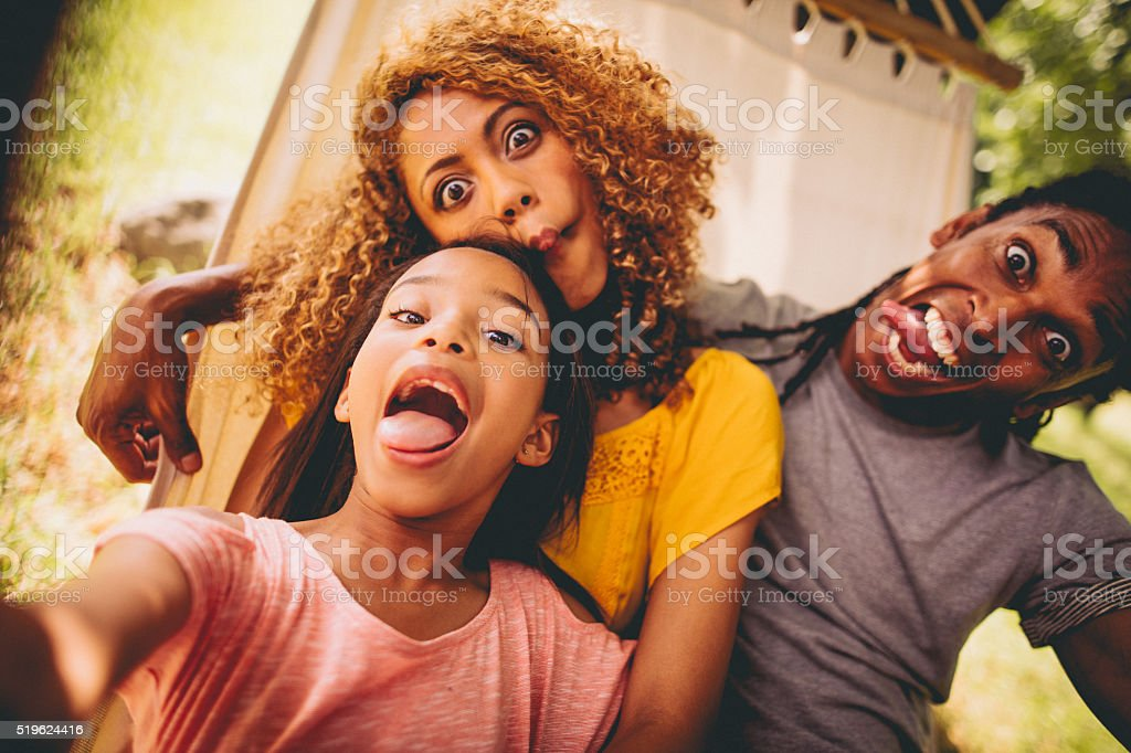 Lovely African-American family making silly faces and posing stock photo
