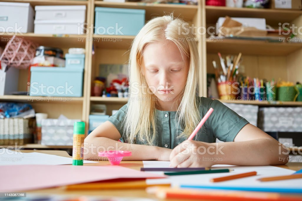 Lovely albino girl drawing good picture with colored pencils while...