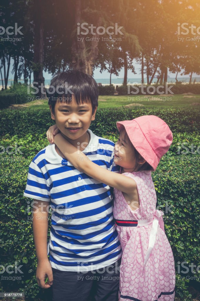 Lovely asian girl put her's arm around brother's shoulder.  Vintage tone. stock photo